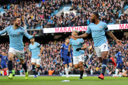 Manchester City players celebrate their first goal of the game scored by Raheem Sterling (right)