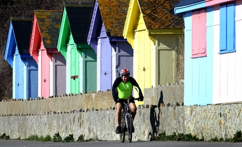 A man rides his bike in the morning sunshine on the promenade in Folkestone, Kent.