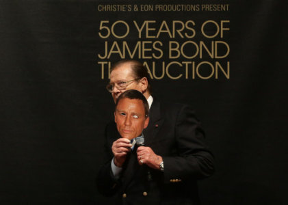 a4f9b6142e3 Sir Roger Moore holds a mask of current James Bond actor Daniel Craig at  Christie s 50