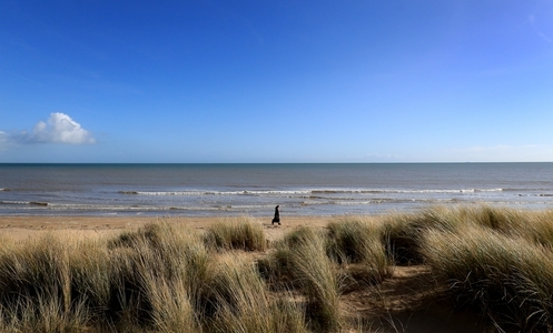 A lady walks in the sunshine along the beach in Greatstone, Kent. Warm weekend weather will see temperatures rise to near record levels for February, the Met Office has said.