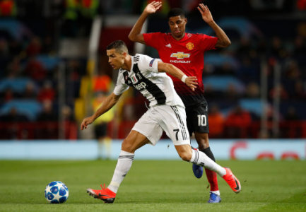 Juventus' Cristiano Ronaldo (left) and Manchester United's Marcus Rashford battle for the ball during the UEFA Champions League match at Old Trafford, Manchester.